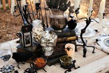 a whimsical Halloween centerpiece of black books, black roses in a vase, eyeballs, a skull, a vintage camera and spiders