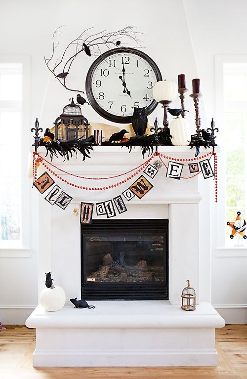 a whimsical Halloween mantel with feathers and blackbirds, white pumpkins, candles, a cage and beads and garlands