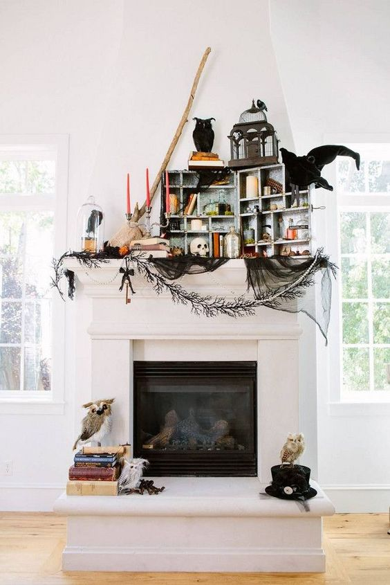 a whimsy Halloween mantel with colorful candles, a box with candles, skulls and apothecary bottles, a cage and faux birds