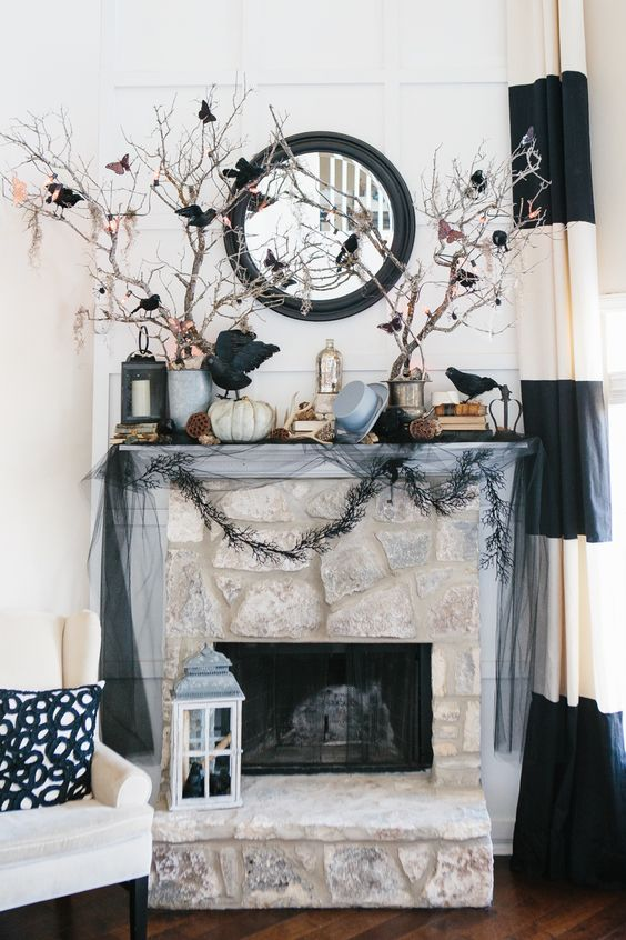 an elegant Halloween mantel with blackbirds, branches with them, a top hat, pumpkins, antlers and lotus
