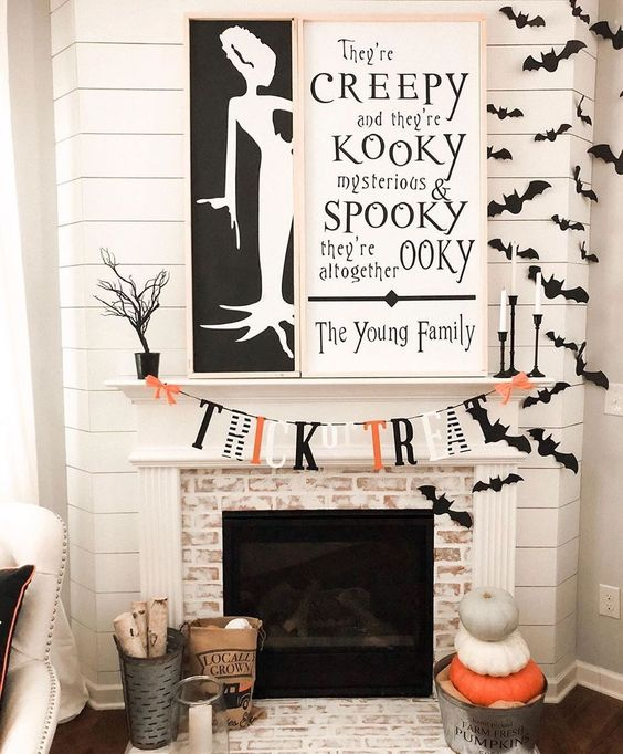 an elegant contrasting fireplace with two monochromatic signs, bats, a bright bunting and stacked pumpkins