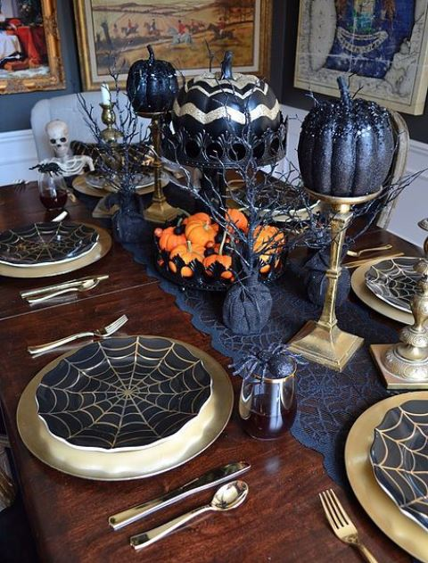 black and gold pumpkins on stands, orange pumpkins on the table and a spiderweb table runner for Halloween