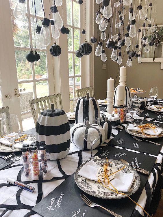 black and white striped pumpkins and candles make up stylish Halloween centerpieces for a modern party