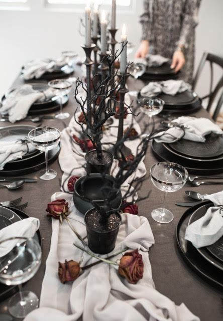 black planters with black branches, black cauldrons, dried roses, grey candles for a Halloween tablescape