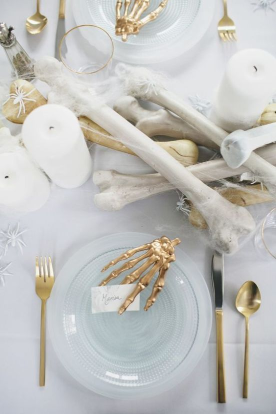 bones, candles, spiders and gold cutlery and a skeleton hand for styling your white and gold Halloween