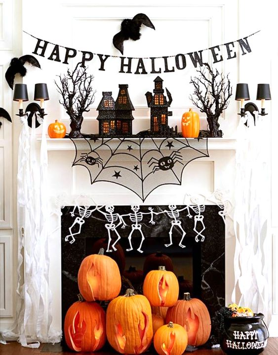 bright Halloween mantel decor with black houses, scary trees, skeletons, bats and cutout pumpkins on the floor