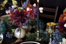 bright blooms greenery, black candles and large eyeballs for a unique Halloween party table