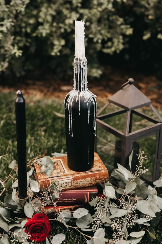 eucalyptus, red roses, books, a black bottle with a candle and a candle lantern for Halloween decor
