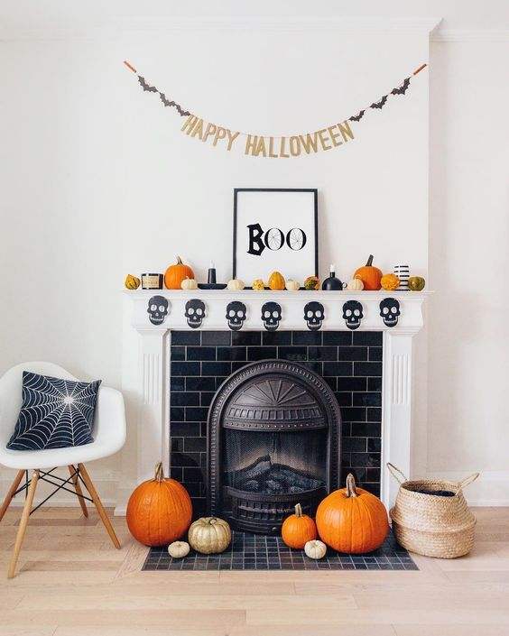 fun and bright Halloween mantel decor with gourds and pumpkins, candles, a banner and a chic sign, pumpkins on the floor