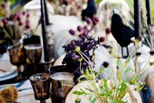 white pumpkins, berries, purple blooms, black candles and crows are ideal to decorate your Halloween table