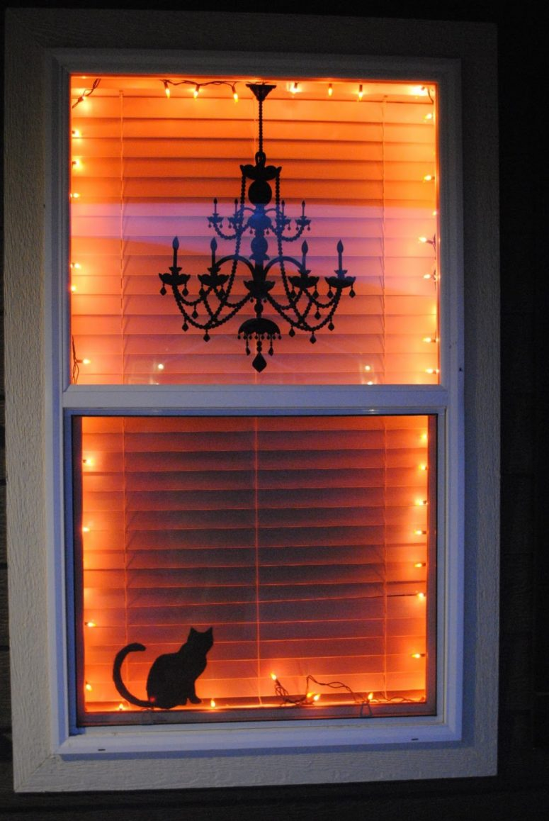 warm lights a chandelier decal and a black cat silhouette is a spooky yet minimalist - Halloween Window Decor