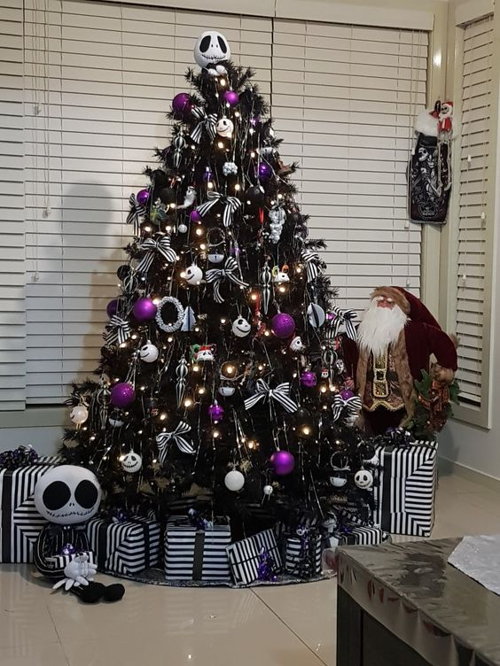 a black Halloween tree with black, white and purple ornaments, with striped bows and lights is very stylish