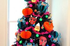 a black Halloween tree with bright paper pumpkins and spiders, scary masks and colorful ornaments