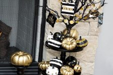 a black Halloween tree with gold garlands, with a stand with black, white and gold pumpkins under it
