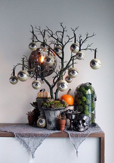a black Halloween tree with lots of eyeballs, with pumpkins and spiders under it is a catchy idea