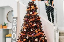 a black Halloween tree with orange ribbons, pumpkins, purple and orange ornaments and glitter pumpkins under it