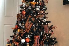 a black Halloween tree with white, black and orange ornaments, skeleton hands, skulls and a sign on top