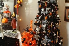 a black lit up Halloween tree, with skeletons, spiders, bright ornaments and a mini orange tree with black ornaments