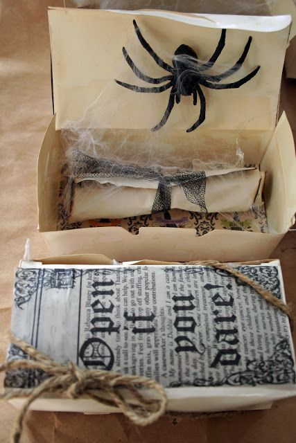 a box with an invite with black lace, a large spider and web, printed papers for a cool look