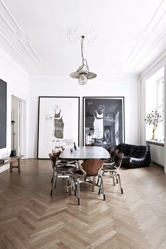 a contemporary monochromatic space done with vintage molding and a medallion plus chic modern furniture