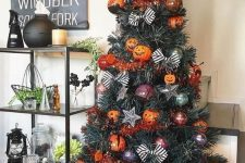 a green Halloween tree with jack-o-lantern ornaments, striped bows, orange garlands is cool