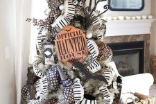 a grey Halloween tree with black and white garlands, signs, witch hats and bats is a bold idea