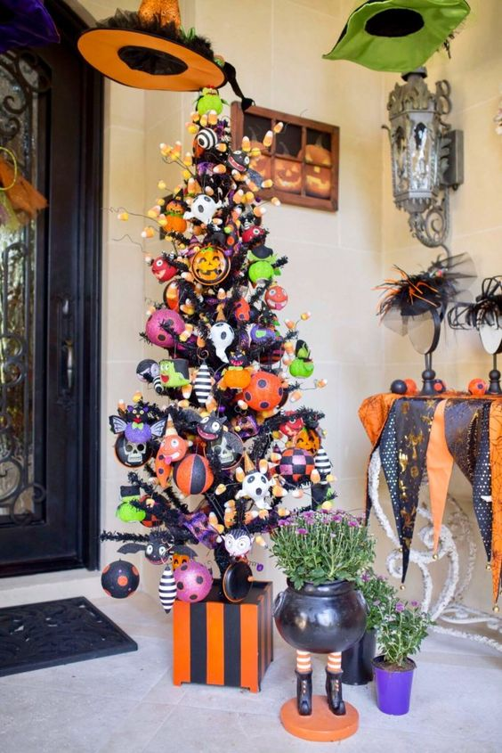 a haunted Halloween tree in black decorated with colorful ornaments, pumpkins, skulls and bats plus candy corns