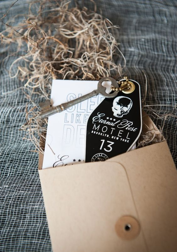 a kraft paper envelope, black and white coffin-shaped invites and a vintage key for a Halloween party