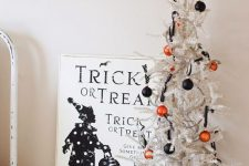 a mini white Halloween tree with orange and black ornaments is a cool and fast decoration for Halloween