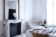 a refined bedroom with vintage molding, a molded fireplace and a mirror frame that echoes with sophisticated furniture