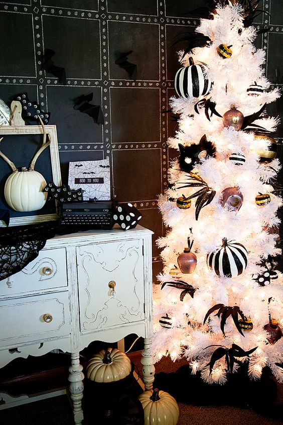 a refined white Halloween tree with striped pumpkins, feathers, ornaments and lights is fantastic