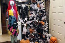 a white Halloween tree with black garlands, pumpkins, plaid ribbons, large jack-o-lanterns, Jack Skellington and his bride