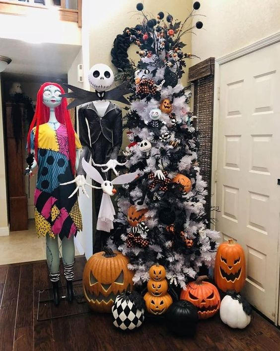 a white Halloween tree with black garlands, pumpkins, plaid ribbons, large jack-o-lanterns, Jack Skellington and his bride