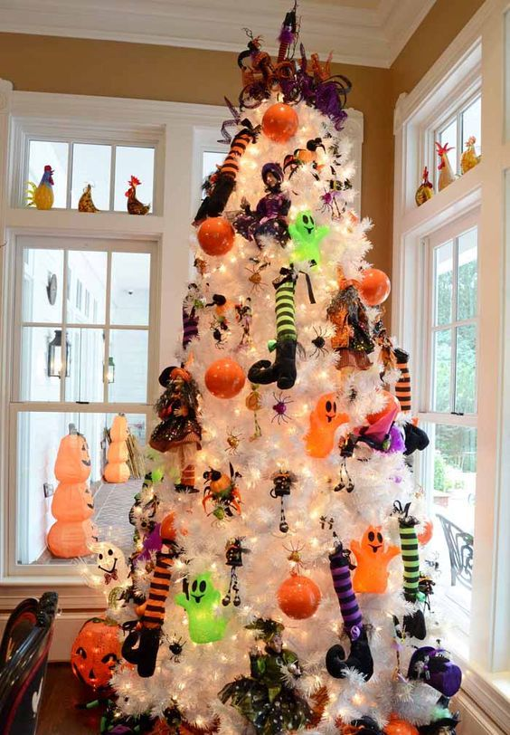 a white Halloween tree with colorful witch legs, hats, dolls and lights plus mini ghosts and bells