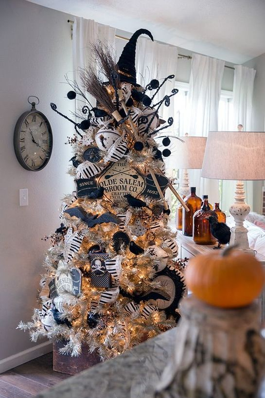 a white Halloween tree with lights, black ornaments, black and white garlands, twigs and a witch hat on top