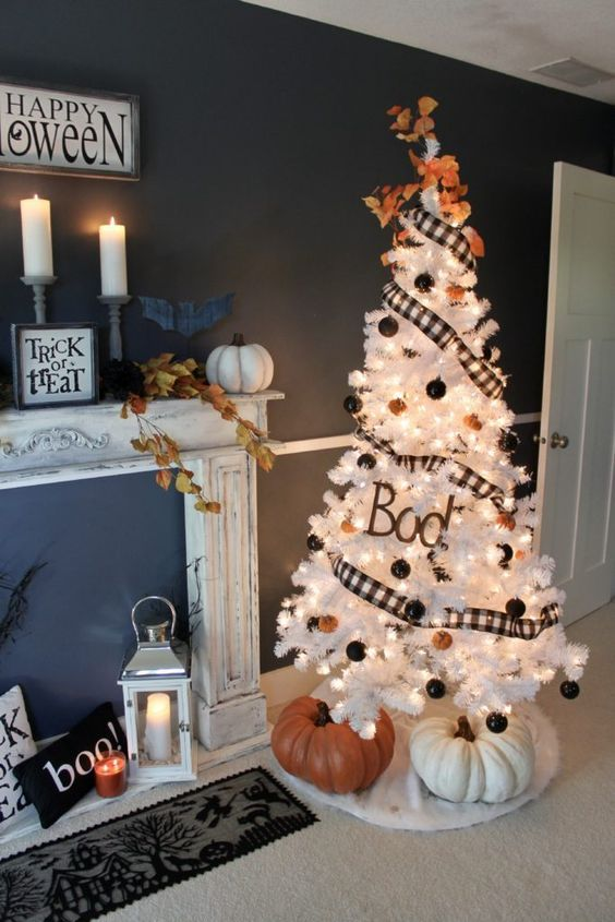 a white Halloween tree with plaid ribbons, orange and black ornaments and large trees under it