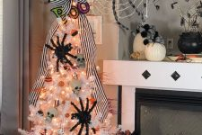 a white Halloween tree with skulls, spiders, lights and mini pumpkins plus a giant web over the tree