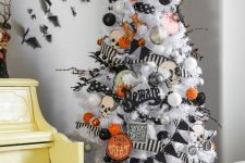 a white Halloween tree with white, grey, silver, orange and black ornaments, garlands and skulls