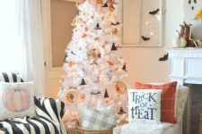 an airy Halloween tree in white, with paper ornaments, bats, witch hats and bold fall leaves on top