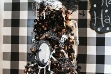 an elegant black Halloween tree with lights, ornaments, skeletons, a mirror and a sign is wow