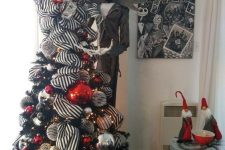 an elegant black Halloween tree with striped garlands, red, silver and black ornaments plus Jack Skellington