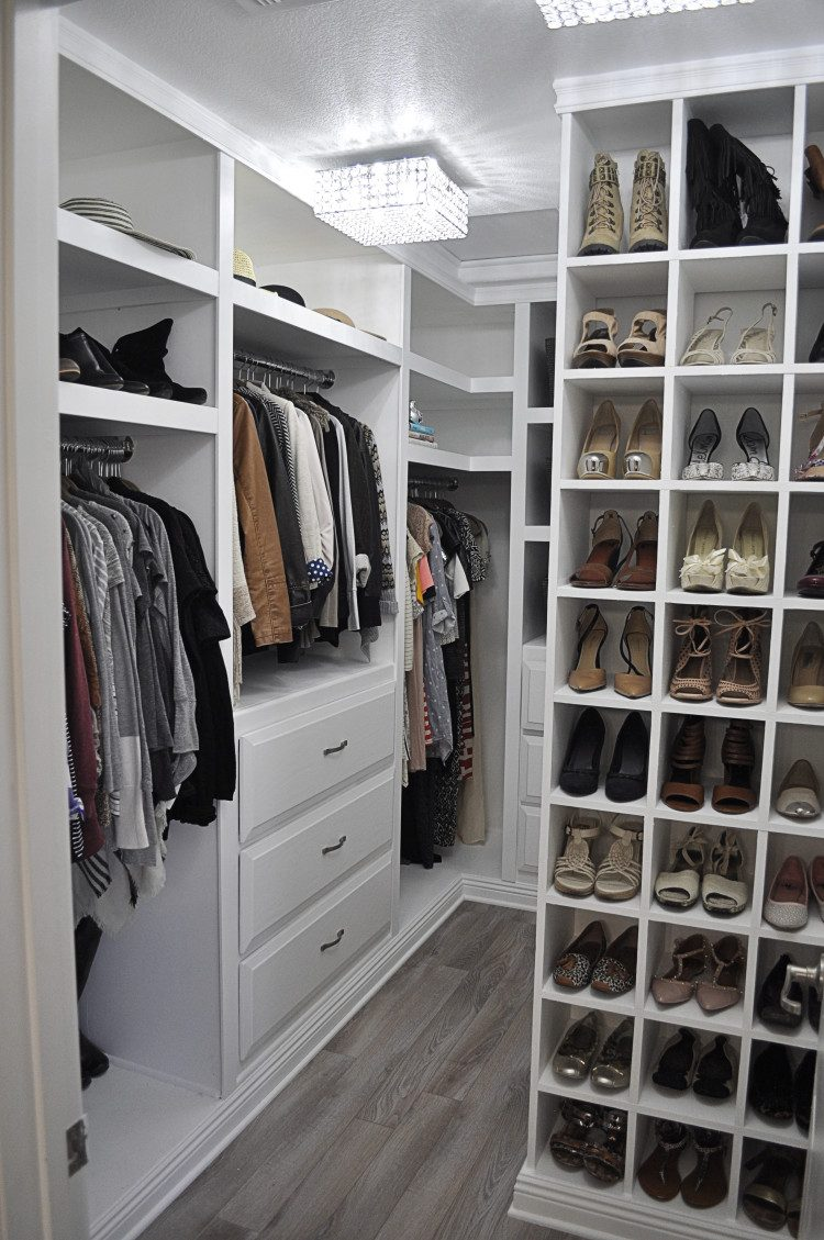 very well organized walk in closet with white cabinets and storage units - Master Closet Design Ideas