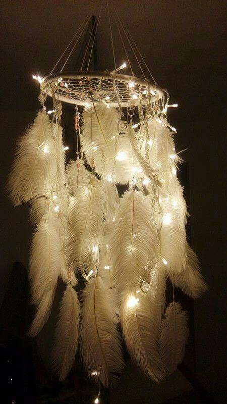 A DIY chandelier made from hula hoop, twine, Christmas lights and plumes is a great addition to any bedroom.