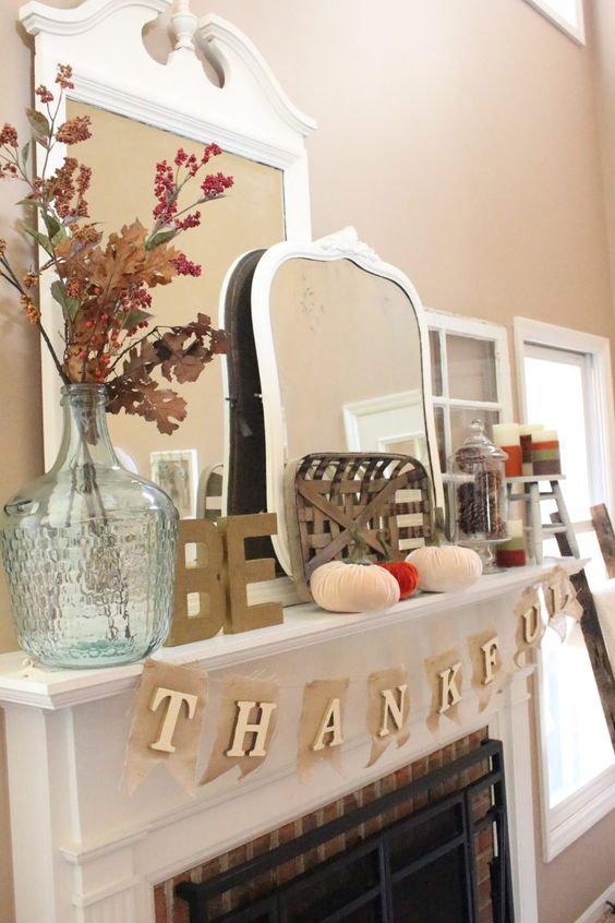 a Thanksgiving mantel with velvet pumpkins, a basket, dried leaves and berries and a burlap banner