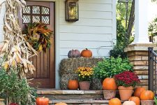 a Thanksgiving porch with corn husks and cobs, potted greenery and blooms, natural pumpkins and baskets