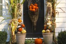 a Thanksgiving porch with orange, white and green pumpkins in cones and on the steps, corn husks and a cornucopia with pumpkins