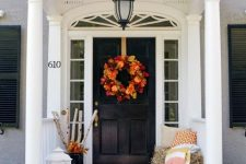 a Thanksgiving porch with white lanterns, orange pumpkins and candles, hay and branches and a fall leaf wreath