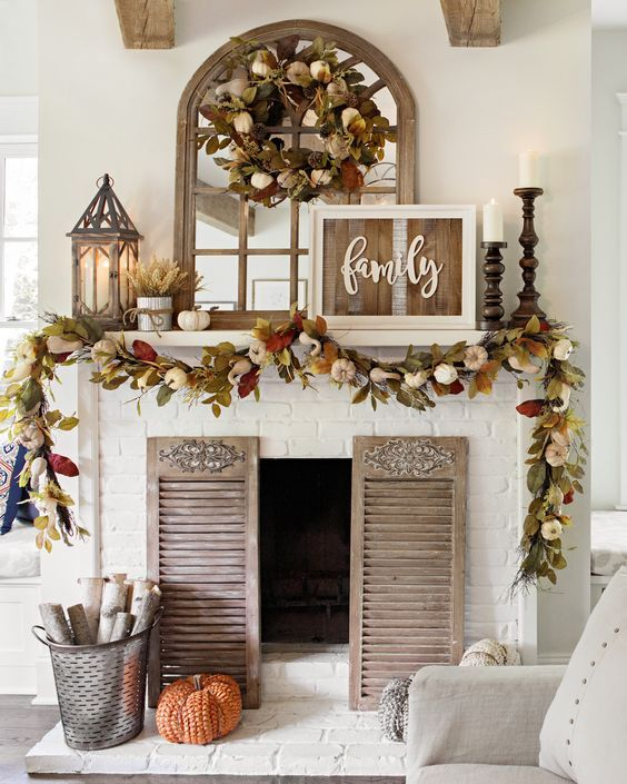 a beautiful Thanksgiving mantel with a lush faux leaf, pumpkins, gourds and lights garland and a wreath, pumpkins, wheat and candles