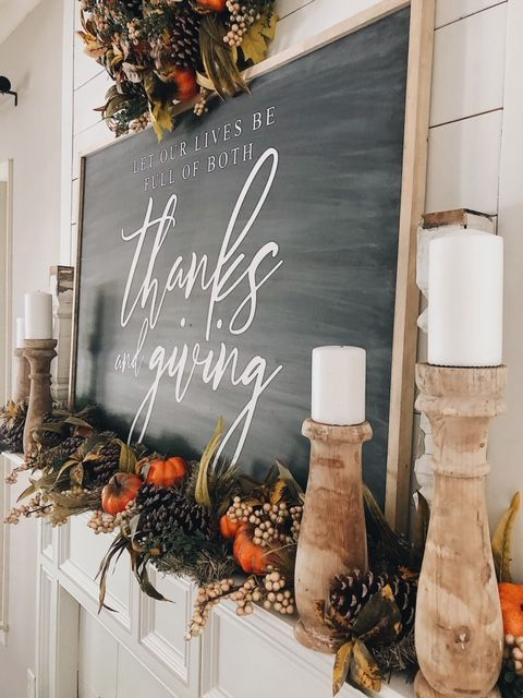 a beautiful rustic Thanksgiving mantel with faux pumpkins, pinecones, berries, faux leaves and greenery, candles and a large sign