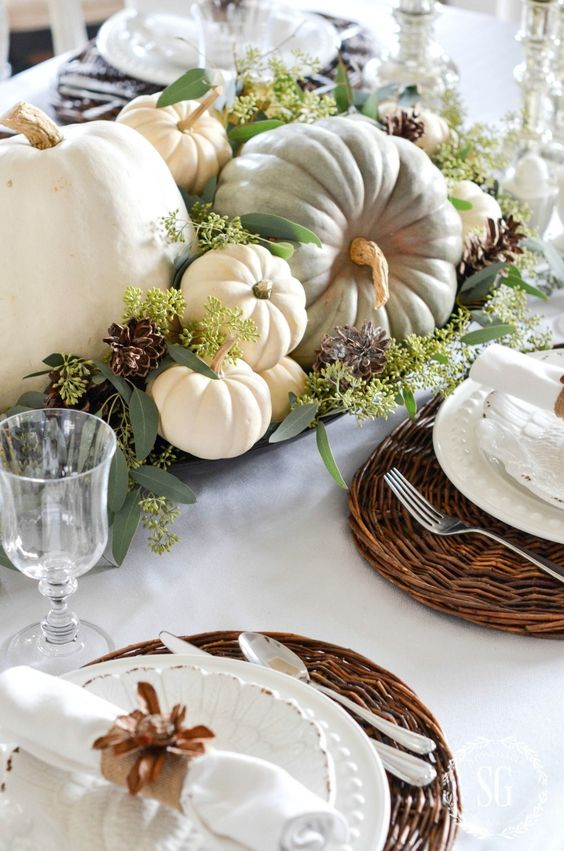 a bowl with eucalyptus, white and green pumpkins and pinecones is a classic Thanksgiving centerpiece